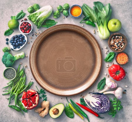 Photo for Healthy food selection with fruits, vegetables, seeds, super foods, cereals and the plate in the middle as copy space - Royalty Free Image