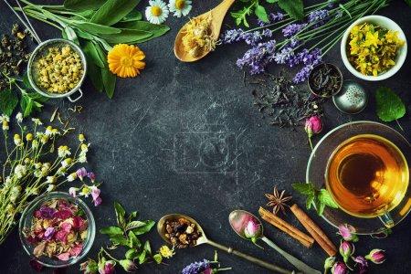 Photo pour Tasse de tisane saine avec menthe, sauge, cannelle, rose séchée, camomille et fleurs de lavande sur fond sombre. Vue du dessus - image libre de droit