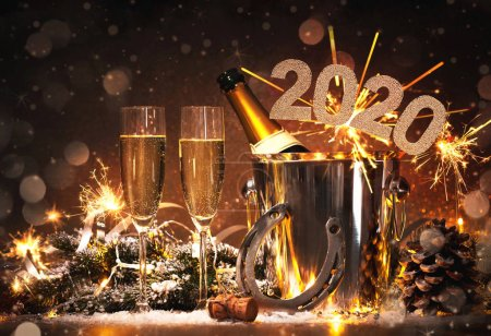 Photo for New Years Eve celebration background with pair of flutes and bottle of champagne in  bucket  and a horseshoe as lucky charm - Royalty Free Image