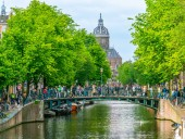 Amsterdam May 18 2018 - The Oudezijdsvoorburgwal channel with in the background tourists crossing by bridge and the old Chruch (Oude Kerk) of Amsterdam