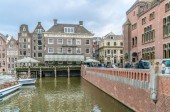Amsterdam May 18 2018 - tourist and locals passing an old trading building now used as the Grasshopper coffeshop