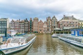 Amsterdam May 18 2018 - tourist and locals waiting for a boat at the Rokin with in the background a row of old traditional houses