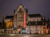 Amsterdam May 18 2018 - tourist and locals visiting the Dam square with in the background the new church at night