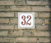 House Number 32 thirty two. brown numbers on a white plate constructed to a old brick wall