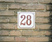 House Number 28 twenty eight. brown numbers on a white plate constructed to a old brick wall