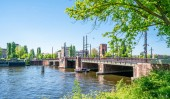 Amsterdam, May 7 2018 - sailers passing with a small boat the Berlage bridge on the river Amstel near the center of Amsterdam in summertime