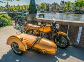 Amsterdam, May 7 2018 - resotred old motorcycle with sidecar parked at the riverside of the river Amstel