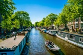 Amsterdam, May 7 2018 - locals sailing with a small boat on the Prinsengracht (prins channel) channel with living boats on a summer day