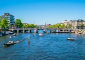Amsterdam, May 7 2018 - view on the river Amstel filled with small boats and the Sarphatistraat bridge on a summer day