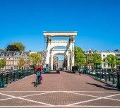 Amsterdam, May 7 2018 - people riding bike crossing the river Amstel over the Magere brug (skinny bridge) on a summer day