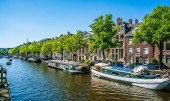 Amsterdam, May 7 2018 - locals sailing with a small boat on the Keizersgracht (Emperors channel) channel with living boats on a summer day