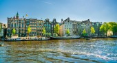 Amsterdam, May 7 2018 - view on the river Amstel filled with small boats and traditional houses in the background on a summer day