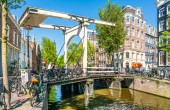 Amsterdam, May 7 2018 - tourist crossing the Groenburgwal over the authentic wodden bridge in the old part of town