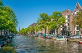 Amsterdam, May 7 2018 - The Prinsengracht with small boats sailing on it and in the background the Westertoren on a sunny day
