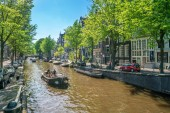 Amsterdam, May 7 2018 - The Prinsengracht with small boats sailing on it on a sunny day