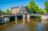 Amsterdam, May 7 2018 - The corner of Prinsengracht and Leidsegracht with tourist enjoying the city at the channels on a sunny day