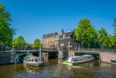 Amsterdam, May 7 2018 - The corner of Prinsengracht and Leidsegracht with tourist boats sailing on the channels on a sunny day