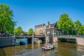 Amsterdam, May 7 2018 - The corner of Prinsengracht and Leidsegracht with small boats sailing on the channels on a sunny day