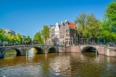 Amsterdam, May 7 2018 - The corner of Keizersgracht and Leidsegracht with tourist enjoying the city at the channels on a sunny day