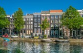 Amsterdam, May 7 2018 - The Keizersgracht with tourist sitting on a bench and traditional buildings on a sunny day
