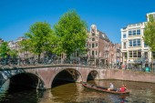 Amsterdam, May 7 2018 - The Keizersgracht with tourist wandering, locals sailing and traditional buildings on a sunny day