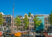 Amsterdam, May 7 2018 - Prinsengracht channel with traditional houses and living boats on a sunny day