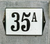 House Number 35A thirty five A, black numbers on a white plate with black border constructed to a old marmer wall