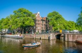 Amsterdam, May 7 2018 - The crossing of the Prinsengracht and the Brouwersgracht  with small boats sailing on it on a sunny day