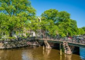 Amsterdam, May 7 2018 - a old bridge crossing the Brouwersgracht with traditional houses on a sunny day
