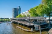 Amsterdam, May 7 2018 - tourist boats on the Prins Hendrikkade with the Ibib Hotel and the big covered bicycle storage building where you can leave your bike when you take the train out of the city