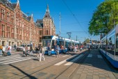 Amsterdam, May 7 2018 - tourist and locals leaving a tram and walking towards the central train station of Amsterdam