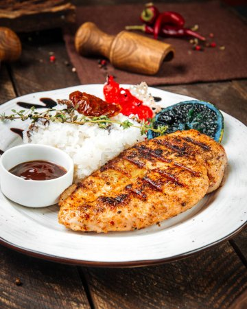Photo pour Closeup on grilled gourmet chicken fillet steak with rice on the wooden table - image libre de droit