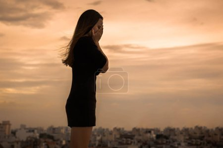 Photo for Woman wearing a black dress is grieving with her hands on her face. City backdrop - Royalty Free Image