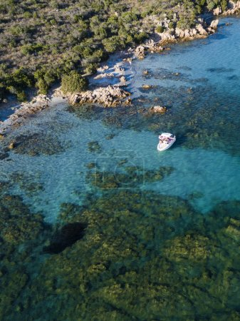 View from above, aerial picture of a boat with some relaxed tourists on board floating on a transparent and turquoise Mediterranean sea. Emerald Coast (Costa Smeralda) in Sardinia, Italy.
