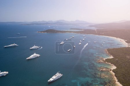 View from above, aerial picture of the amazing Emerald Coast with a turquoise and transparent Mediterranean sea full of luxury yachts and boats during the summer season, Sardinia, Italy.