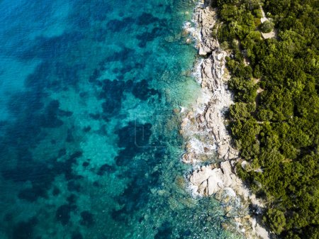 Aerial view of an amazing rocky and green coast bathed by a transparent and turquoise sea. Sardinia, Italy.