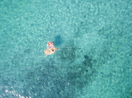 Aerial view of two people relaxed on an inflatable mat floating on a beautiful turquoise sea. Cala Brandinchi, Sardinia, Italy.