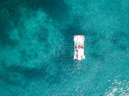 Aerial view of some relaxed people on a pedalos floating on a beautiful turquoise sea. Cala Brandinchi, Sardinia, Italy.