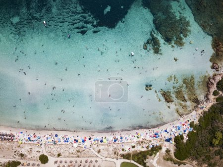 Aerial view of a white beach full of colored beach umbrellas and relaxed people swimming on a clear sea. Cala Brandinchi, Sardinia, Italy.
