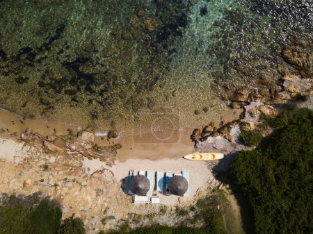 Aerial view of two beach umbrellas on a beautiful small beach bathed by a beautiful turquoise sea. Sardinia, Italy.