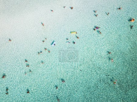 Aerial view of relaxed people swimming on a clear  and transparent sea. Cala Brandinchi, Sardinia, Italy.