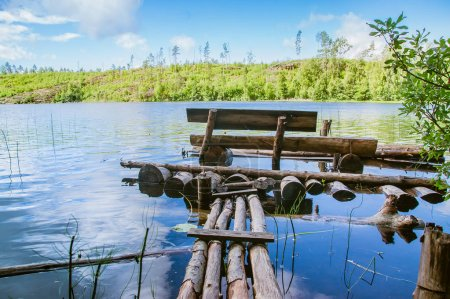 wooden bench and a planked footway on a quiet pond, a fishing place