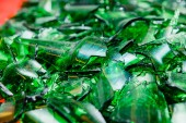pile of pieces of broken green bottle glass