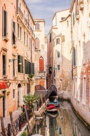 VENICE, ITALY - 11 SEPTEMBER, 2016: Narrow canal with moored boats near small bridge