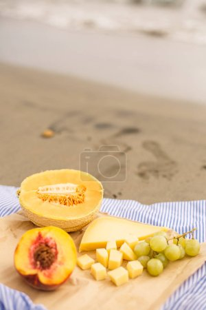 Cut peach, melon, grapes and cheese. Health lunch on sandy beach.
