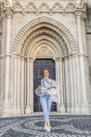 Young redhead girl posing near medieval portal of cathedral in Budapest, Hungary
