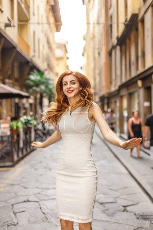 Attractive redhead woman in jump on narrow european street