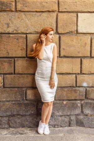 Photo pour Belle femme rousse posant avant vieux mur de briques de calcaire - image libre de droit