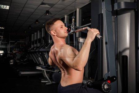 Photo pour Jeune athlète masculin musculation en bleu vêtements de sport faire des exercices avec haltères dans une salle de gym sombre - image libre de droit