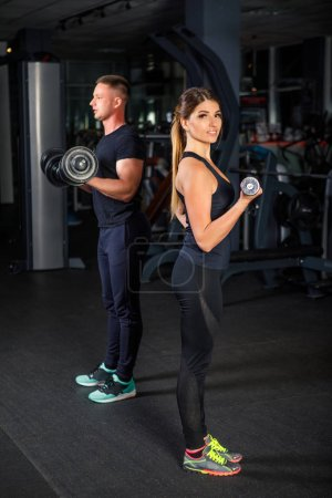 young beautiful couple sportsmen in sportswear doing exercises in a dark gym